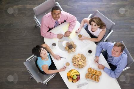 Four businesspeople at boardroom table with breakfast smiling stock photo,  by Monkey Business Images