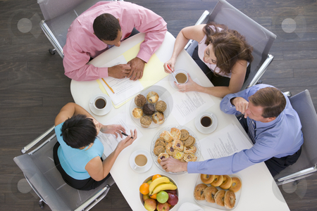Four businesspeople at boardroom table with breakfast stock photo,  by Monkey Business Images