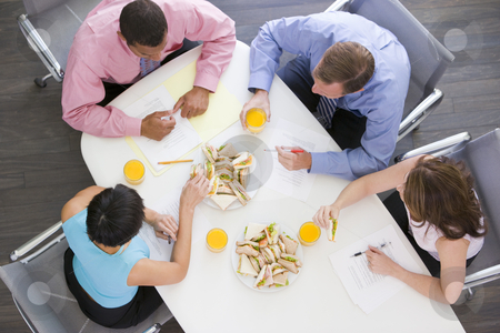 Four businesspeople at boardroom table with sandwiches stock photo,  by Monkey Business Images