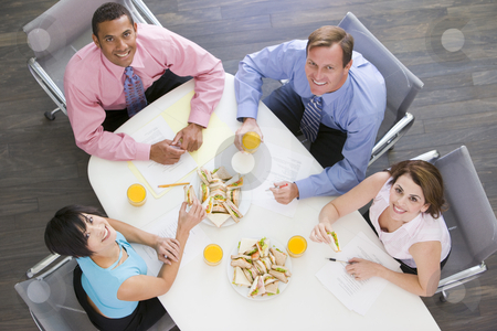 Four businesspeople at boardroom table with sandwiches smiling stock photo,  by Monkey Business Images