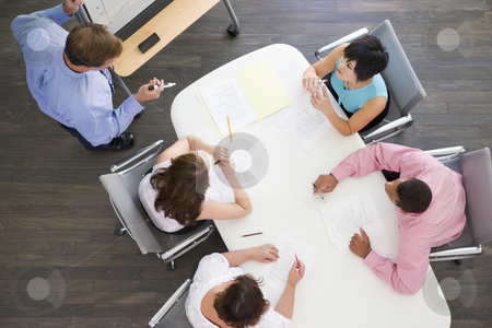Four businesspeople at boardroom table watching presentation stock photo,  by Monkey Business Images