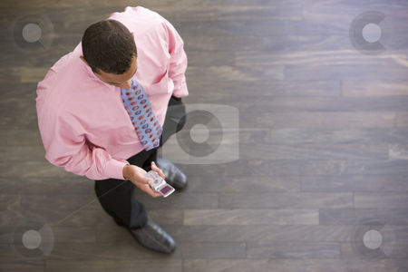 Businessman standing indoors looking at cellular phone stock photo,  by Monkey Business Images