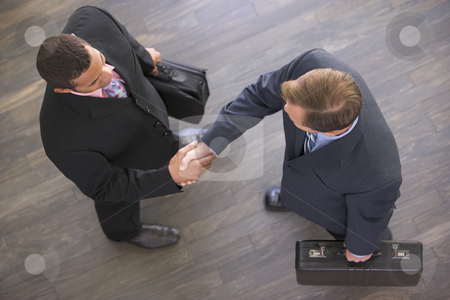 Two businessmen indoors shaking hands stock photo,  by Monkey Business Images