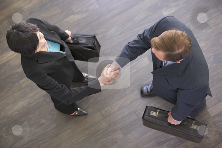 Two businesspeople indoors shaking hands stock photo,  by Monkey Business Images