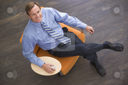 Businessman sitting indoors with cellular phone smiling stock photo,  by Monkey Business Images