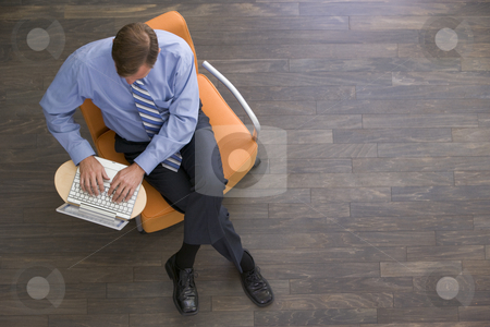 Businessman sitting indoors with laptop stock photo,  by Monkey Business Images