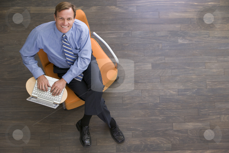 Businessman sitting indoors with laptop smiling stock photo,  by Monkey Business Images