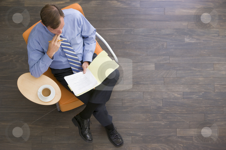 Businessman sitting indoors with coffee and folder stock photo,  by Monkey Business Images
