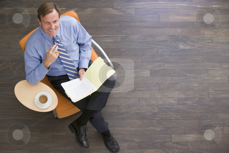 Businessman sitting indoors with coffee and folder smiling stock photo,  by Monkey Business Images