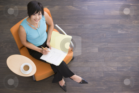Businesswoman sitting indoors with coffee and folder smiling stock photo,  by Monkey Business Images