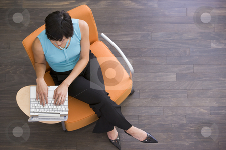 Businesswoman sitting indoors with laptop stock photo,  by Monkey Business Images