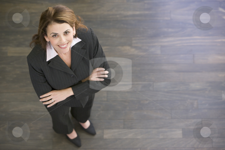 Businesswoman standing indoors smiling stock photo,  by Monkey Business Images