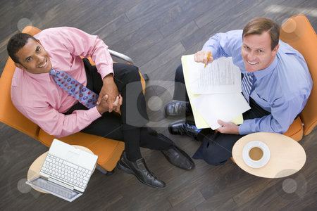 Two businessmen sitting indoors with coffee laptop and folder sm stock photo,  by Monkey Business Images