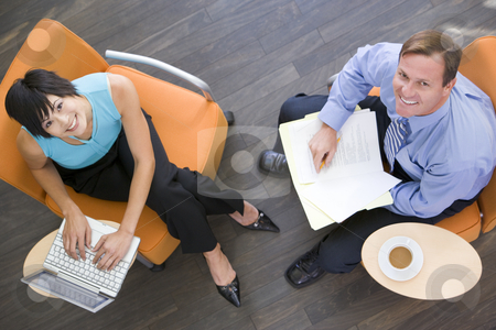 Two businesspeople sitting indoors with coffee laptop and folder stock photo,  by Monkey Business Images