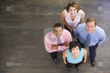 Four businesspeople standing indoors smiling stock photo,  by Monkey Business Images