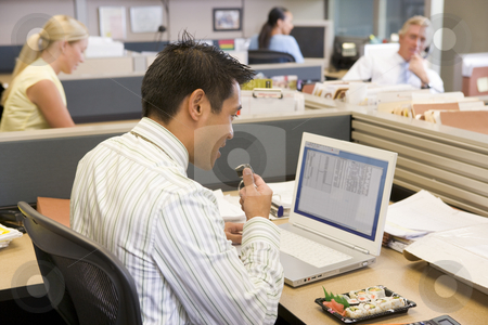 Businessman in cubicle at laptop eating sushi stock photo,  by Monkey Business Images