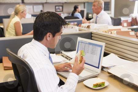 Businessman in cubicle at laptop eating sandwich stock photo,  by Monkey Business Images