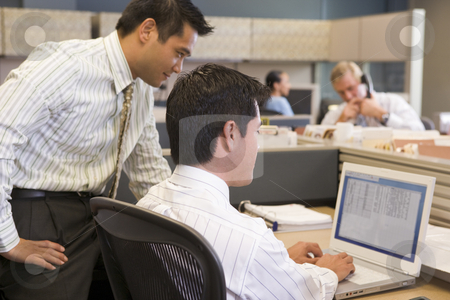 Two businessmen in cubicle looking at laptop stock photo,  by Monkey Business Images