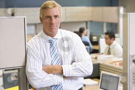 Businessman standing in cubicle stock photo,  by Monkey Business Images