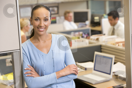 Businesswoman standing in cubicle smiling stock photo,  by Monkey Business Images