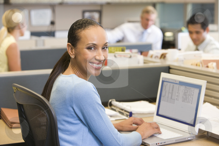 Businesswoman in cubicle using laptop smiling stock photo,  by Monkey Business Images