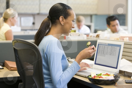 Businesswoman in cubicle eating sushi smiling stock photo,  by Monkey Business Images