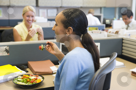 Businesswoman in cubicle eating salad and smiling stock photo,  by Monkey Business Images