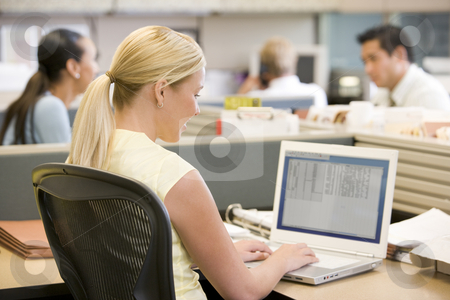 Businesswoman in cubicle using laptop stock photo,  by Monkey Business Images