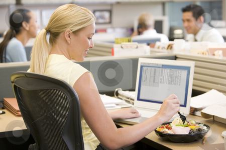 Businesswoman in cubicle using laptop and eating salad stock photo,  by Monkey Business Images