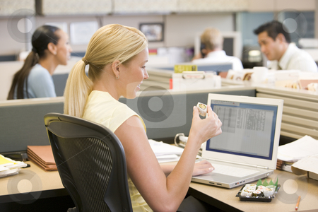 Businesswoman in cubicle using laptop eating sushi stock photo,  by Monkey Business Images