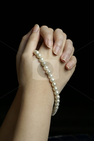 Hands in prayer with pearls stock photo, Hands in prayer with pearls on black by Wong Chee Yen