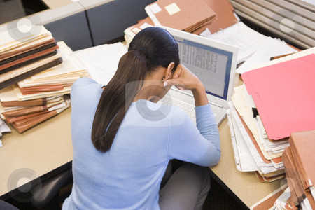 Businesswoman in cubicle with laptop and stacks of files stock photo,  by Monkey Business Images