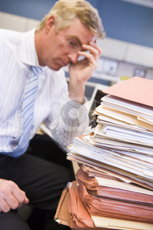Businessman in cubicle with laptop and stacks of files stock photo,  by Monkey Business Images