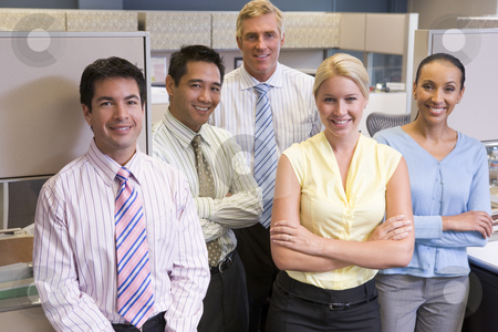 Business team standing in cubicle smiling stock photo,  by Monkey Business Images