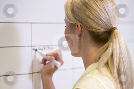 Businesswoman indoors writing on erasable board stock photo,  by Monkey Business Images