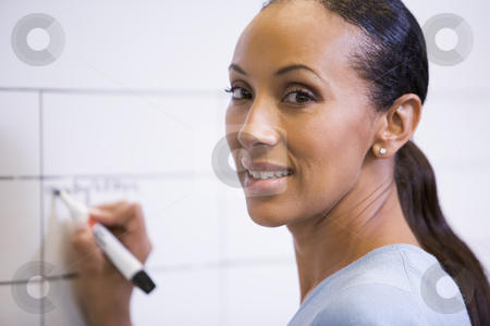 Businesswoman indoors writing on erasable board smiling stock photo,  by Monkey Business Images
