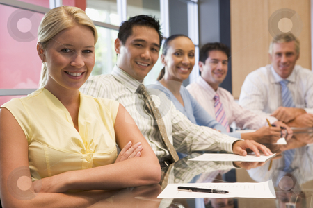 Five businesspeople at boardroom table smiling stock photo,  by Monkey Business Images