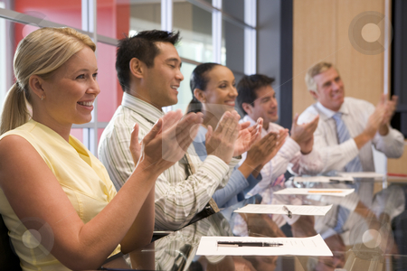 Five businesspeople at boardroom table applauding and smiling stock photo,  by Monkey Business Images