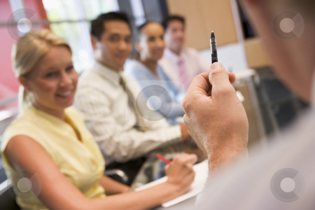 Five businesspeople at boardroom table with focus on businessman stock photo,  by Monkey Business Images