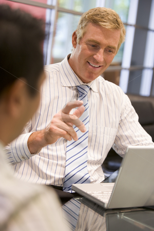 Two businessmen in boardroom with laptop talking stock photo,  by Monkey Business Images