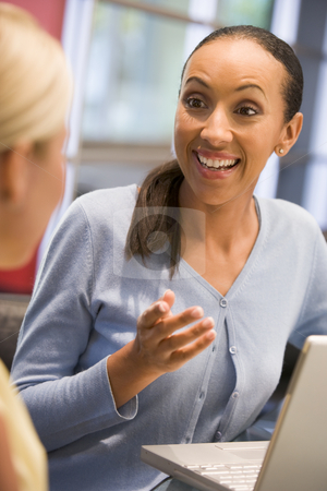 Two businesswomen in boardroom with laptop talking stock photo,  by Monkey Business Images