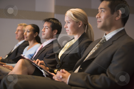 Five businesspeople sitting in presentation room with clipboards stock photo,  by Monkey Business Images