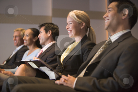 Five businesspeople smiling in presentation room with clipboards stock photo,  by Monkey Business Images