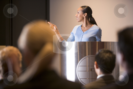 Businesswoman giving presentation at podium stock photo,  by Monkey Business Images
