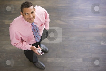 Businessman standing indoors with cellular phone smiling stock photo,  by Monkey Business Images