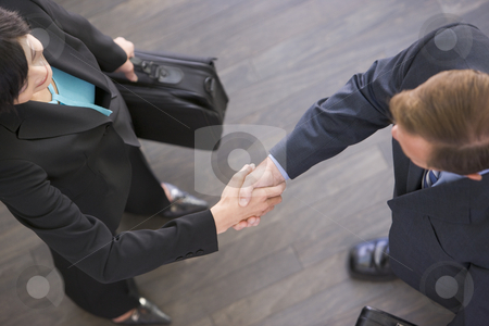 Two businesspeople standing indoors shaking hands stock photo,  by Monkey Business Images