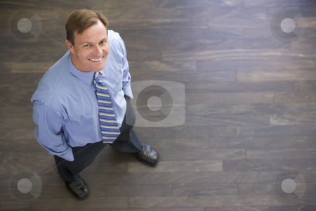 Businessman standing indoors smiling stock photo,  by Monkey Business Images