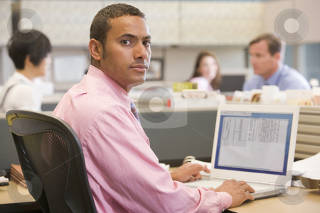 Businessman in cubicle with laptop stock photo,  by Monkey Business Images