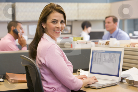 Businesswoman in cubicle smiling stock photo,  by Monkey Business Images