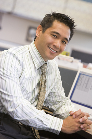 Businessman in cubicle smiling stock photo,  by Monkey Business Images